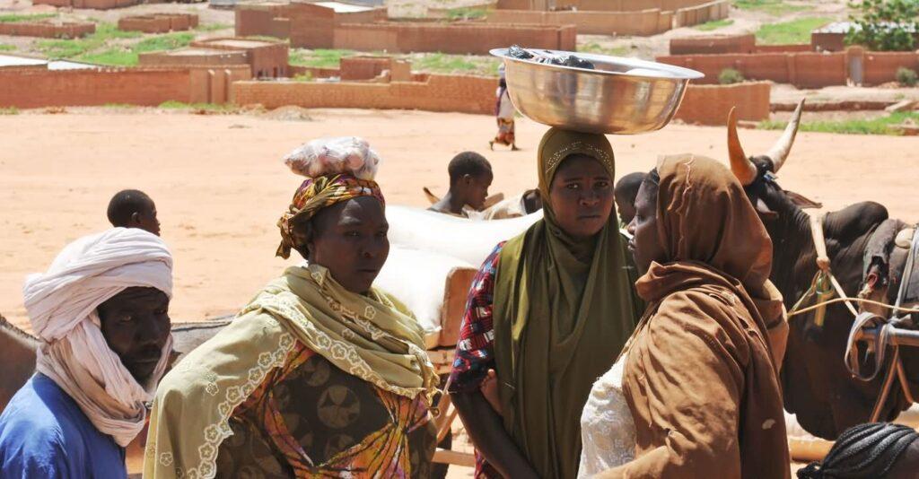 Frauen auf dem Markt von Kara Kara, im Hintergrund Lehmhütten